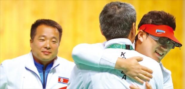 진종오(맨 오른쪽)가 11일(한국시간) 리우올림픽 남자 50m 권총 결선에서 베트남의 호앙쑤언빈을 꺾고 금메달을 확정 지은 뒤 박병택 코치와 포옹하고 있다. 동메달을 차지한 북한의 김성국(맨 왼쪽)이 미소를 지으며 지켜보고 있다. 연합뉴스