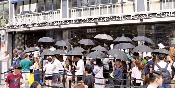 14일 쉑쉑버거 매장 앞에 양산을 든 고객들이 줄을 서 있다.