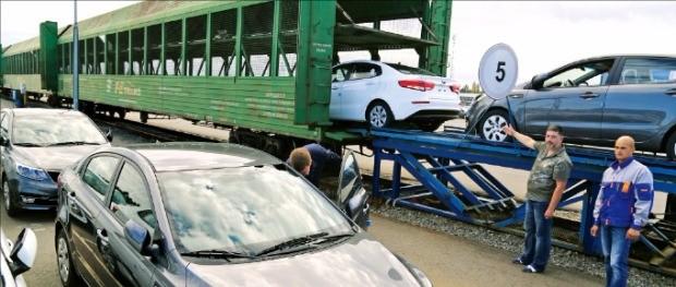 글로비스 직원들이 지난 12일 러시아 벨로스트로프역에서 열차에 자동차를 싣고 있다. 김순신 기자