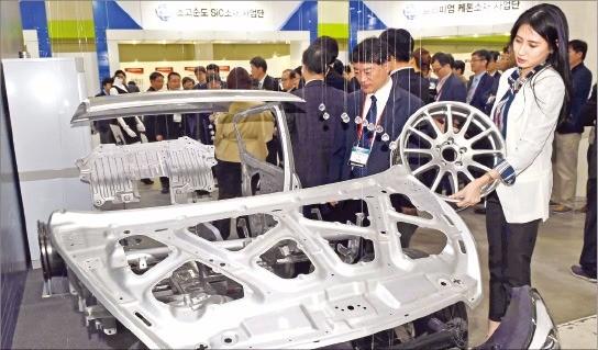 지난 4월 서울 코엑스에서 열린 '세계 일류 소재개발 사업성과 전시회'에서 업계 관계자들이 마그네슘 소재로 만든 자동차용 강판 등을 살펴보고 있다. 한경DB