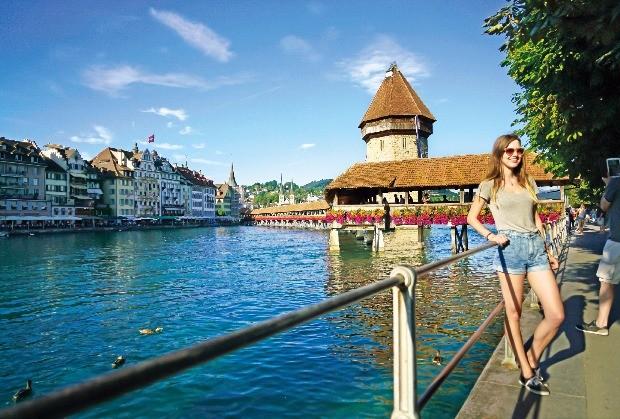 로이스강을 가로지르는 스위스 루체른의 카펠교를 배경으로 관광객이 사진을 찍고 있다.