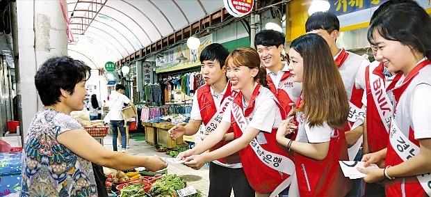 경남은행 직원들과 제5기 대학생 홍보대사들이 거제 고현시장에서 전통시장 살리기 캠페인을 펼치고 있다.  경남은행 제공