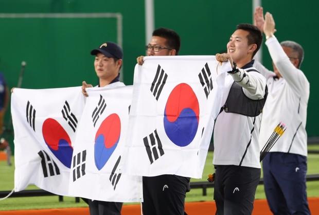 (리우데자네이루=연합뉴스) 임헌정 기자 = 6일 오후(현지시간) 브라질 리우데자네이루 삼보드로모 경기장에서 열린 2016 리우올림픽 남자양궁 단체전 결승에서 미국을 꺾고 금메달을 차지한 한국 대표팀의 구본찬(오른쪽부터), 김우진, 이승윤이 태극기를 들고 관중에게 인사하고 있다.