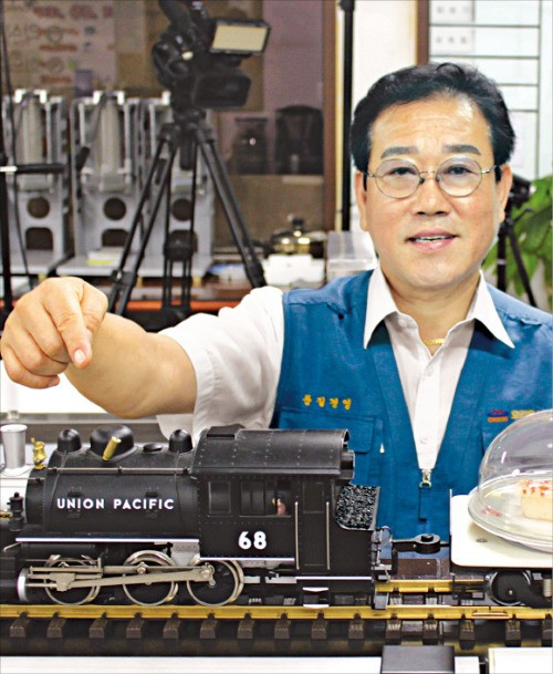 엄천섭 오리온식품기계 사장이 소형 장난감 기차를 이용한 음식배달 시스템을 설명하고 있다. 김낙훈 기자
