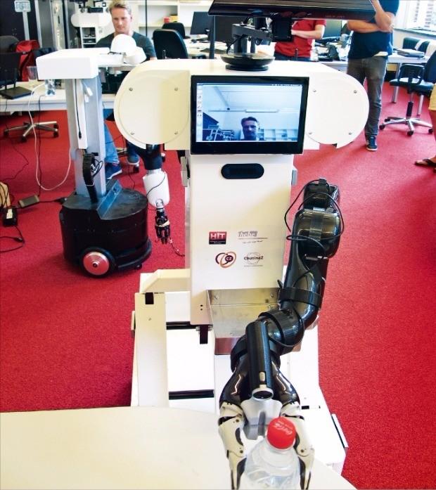 네덜란드 델프트공대 내 로보밸리에 입주한 로봇 스타트업 힘스케르크이노버티브테크놀로지(HIT)의 간병 로봇이 원격 지시에 따라 물병을 집어서 기자에게 건네주고 있다. 로봇 상단 모니터에 뒤에서 명령을 내리고 있는 엔지니어의 얼굴이 보인다. 델프트=이상은  기자