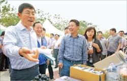 이상훈 삼성전자 사장(최고재무책임자·왼쪽)이 6일 추석맞이 자매마을 직거래 장터에서 송산포도를 사고 있다.