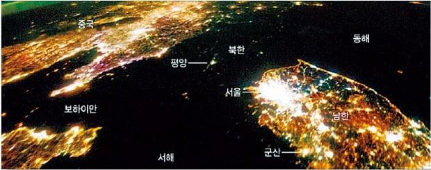 """지난 2014년 1월 미국 항공우주국(NASA)이 우주정거장에서 찍은 한반도 밤사진. 남쪽에서는 불빛이 쏟아져 나오고 있지만 북한은 평양을 제외하고는 깜깜하다. 미국항공우주국은 """"야간 사진에 나타나는 불빛은 경제의 중요성을 극적으로 보여준다""""고 설명했다."""