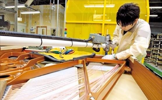일본 시즈오카현 하마마쓰의 야마하 악기 공장에서 기술자가 피아노 프레임에 현을 고정시키고 있다.