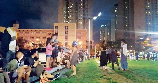 < 지진에 잠 못 이루는 밤 > 경북 경주에서 지진이 잇따라 발생한 12일 오후 부산 해운대 센텀시티 문화복합센터 앞 잔디밭에 인근 주민 수백명이 대피해 있다. 연합뉴스