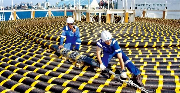 LS전선 동해사업장 엔지니어들이 카타르 석유공사에 납품할 해저케이블 완제품을 살피고 있다.