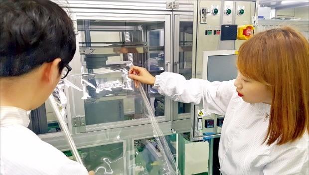 코오롱인더스트리 직원들이 투명 폴리이미드 필름을 점검하고 있다.