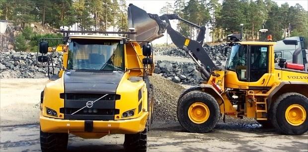 무인 자율주행 기능을 갖춘 휠로더 L120(오른쪽)이 무인 자율주행 트럭 A25에 석재를 싣고 있다. 안대규 기자