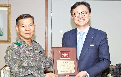 유상호 한국투자증권 사장(오른쪽)은 지난해 2월 서울 여의도 한국투자증권 본사에서 박일재 준장(전 3기갑 여단장)으로부터 '1사1병영 국방부장관 감사패'를 받았다. 한국투자증권 제공