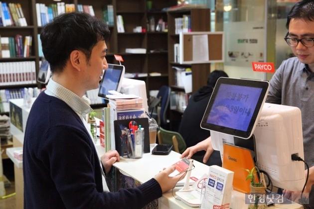 김현준씨가 경희대 교내 서점에서 교재를 구매하면서 간편결제 서비스 '페이코'를 이용하고 있다.