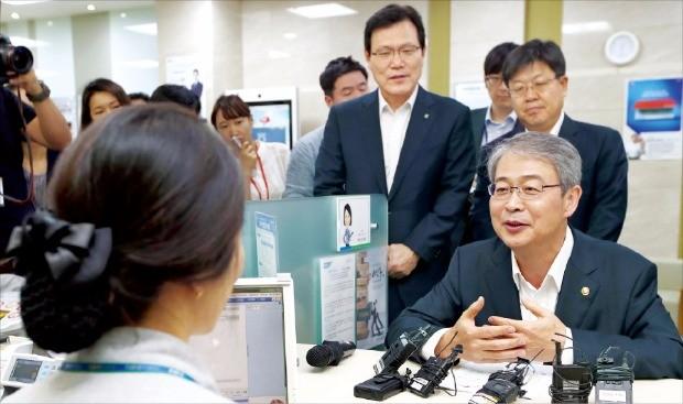 임종룡 금융위원장(오른쪽)은 지난 7월 서울 NH농협은행 광화문지점을 찾아 서민층을 위한 중금리대출 상품인 사잇돌 대출 판매 현황을 점검했다. 한경DB