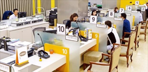 정부가 금융회사의 성과주의 연봉제 도입을 추진하면서 노사 갈등이 빚어지고 있다. 전국금융산업노동조합이 일일 총파업을 벌인 지난달 23일 서울 명동의 한 시중은행 지점 직원들이 고객을 맞고 있다. 한경DB