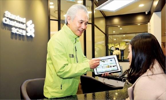 박종복 SC제일은행장(왼쪽)이 지난 1월 부산 신세계백화점 센텀시티점에 처음 문을 연 초소형 점포 '뱅크샵'에서 1호 고객에게 태블릿PC 기반의 플랫폼을 활용해 금융상담을 하고 있다. SC제일은행  제공