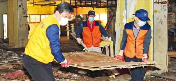 주영섭 중소기업청장(왼쪽)이 9일 태풍 차바로 침수 피해가 큰 울산 태화시장을 찾아 중소기업청 임직원들과 복구활동을 하고 있다. 중소기업청 제공