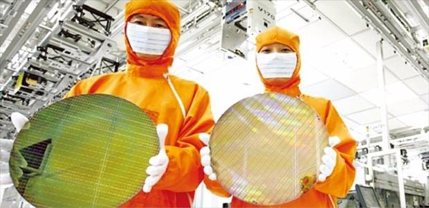 SK하이닉스 직원들이 경기 이천 공장에서 생산한 반도체를 들어보이고 있다.