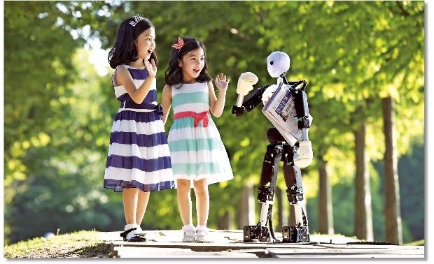 이세돌 9단과 인공지능 로봇 알파고의 바둑대국은 세계적 관심사였다. 결과는 인공지능의 승. 이는 '4차 산업혁명'의 시작을 알리는 신호탄이었다. '로봇과 인간이 이제는 같은 공간에서 같이 호흡하며 살아갈 날이 다가오고 있다'는 생각으로 촬영한 사진. 이수연 어린이(8세·왼쪽)와 이지윤 어린이(6세)가 서울 성동구 서울숲 공원에서 SK텔레콤의 5G 로봇과 함께 손을 흔들며 인사하고 있다. 김범준 기자  bjk07@hankyung.com