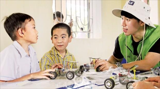 LS 대학생 봉사단 소속 학생이 베트남에서 현지 초등학생과 태양광 자동차 키트를 만들고 있다.