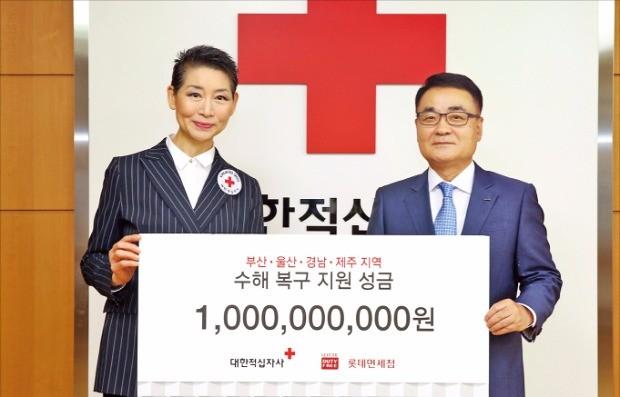 장선욱 롯데면세점 대표(오른쪽)가 지난 7일 김성주 대한적십자사 총재에게 수해 복구 지원금을 전달하고 있다.