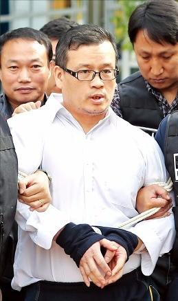 사제 총기로 경찰을 살해한 성병대(46)가 서울북부지방법원에서 구속전 피의자 심문을 받은 뒤 경찰 호송차로 이동하고 있다. 연합뉴스
