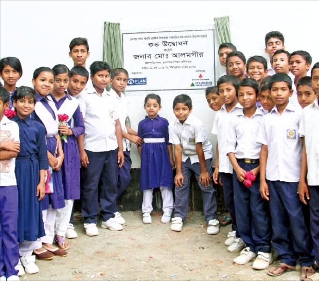 현대건설이 방글라데시에 증축한 공립 초등학교 학생들이 기념사진을 찍고 있다.