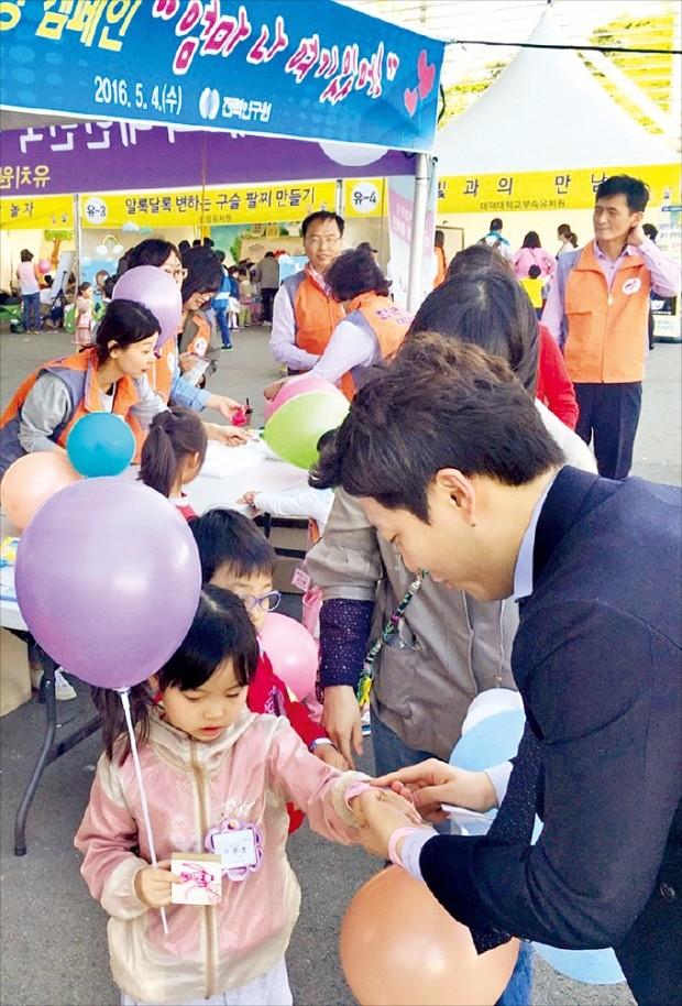 미아 예방 캠페인에 참여한 한국전력 직원들이 유치원생들에게 이름표가 적힌 미아 예방 종이 팔찌를 나눠주고 있다.
