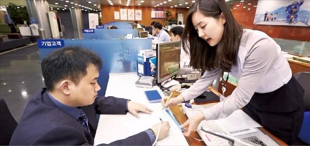 기업은행 직원이 본점 영업부 창구에서 고객에게 금융상품의 특징과 유의점을 설명하고 있다. 기업은행 제공