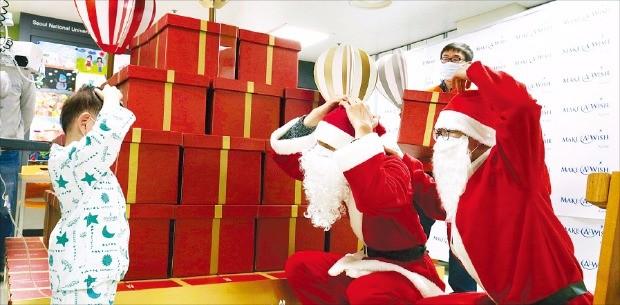 지난해 크리스마스 산타 복장을 한 한화갤러리아 임직원들이 서울대병원 어린이병동 환아들에게 선물을 나눠주고 있다.