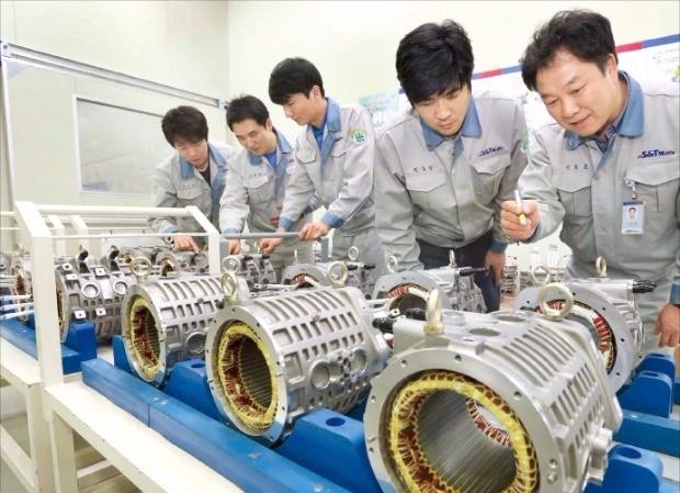 S&T모티브 직원들이 부산 본사 자동차부품 생산공장에서 친환경 모터의 품질 검사를 하고 있다. S&T모티브 제공.