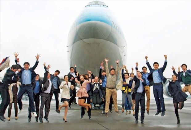 대한항공 신입사원들이 비행기 앞에서 힘찬 날갯짓을 하고 있다.