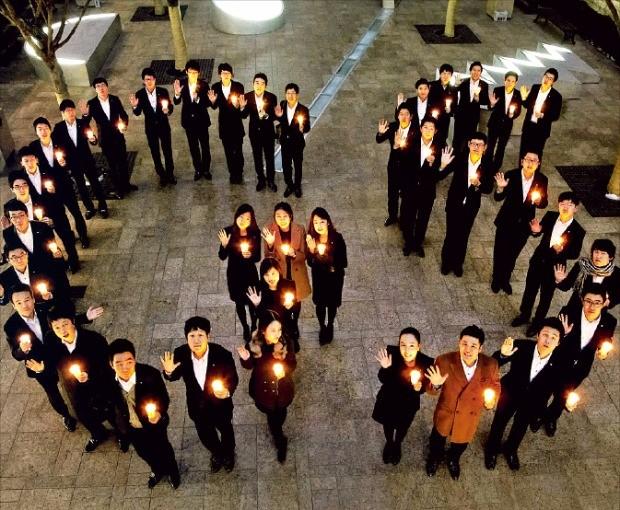 GS칼텍스 신입사원들이 촛불을 들고 'GS'라는 글자를 만들어 보이고 있다.