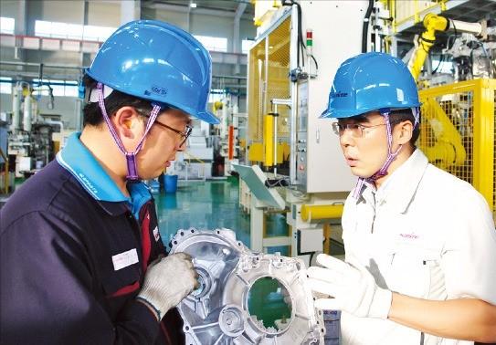 김치환 삼기오토모티브 사장(오른쪽)이 직원과 함께 자동차 변속기 부품을 살펴보고 있다. 삼기오토모티브  제공
