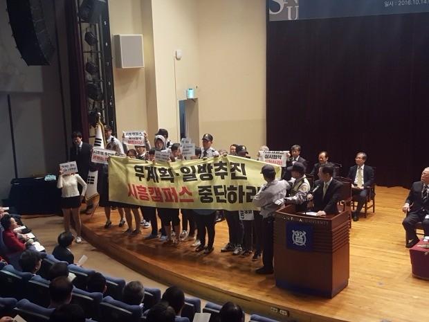 서울대 시흥캠퍼스 추진에 반대하는 학생들이 14일 교내에서 열린 '개교 70주년 기념식' 도중 단상에 올라가 시위하고 있다.