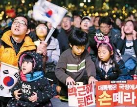 """< """"내 아이의 미래를 위해"""" > 자녀들과 함께 주말 촛불집회에 참가한 한 시민이 태극기를 흔들고 있다. 김범준 기자 bjk07@hankyung.com"""