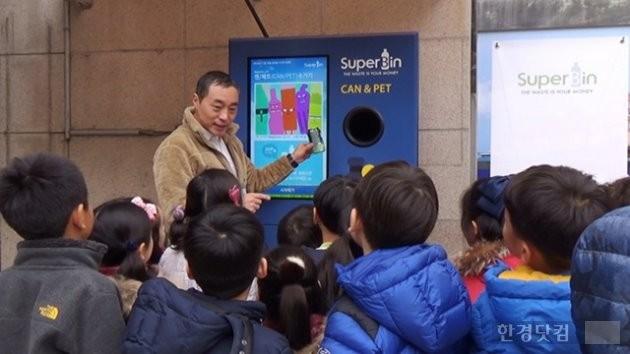 김정빈 수퍼빈 대표가 어린이들에게  AI 기반의 재활용 자판기 '네프론' 사용법을 설명하고 있다.