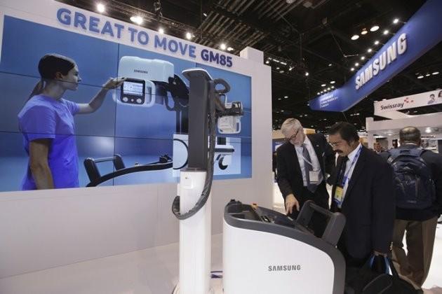 미국 시카고에서 열린 제 102회 북미영상의학회(RSNA)에서 삼성전자 부스를 방문한 참관객들이 이동형 엑스레이 'GM85'에 대한 설명을 듣고 있다.