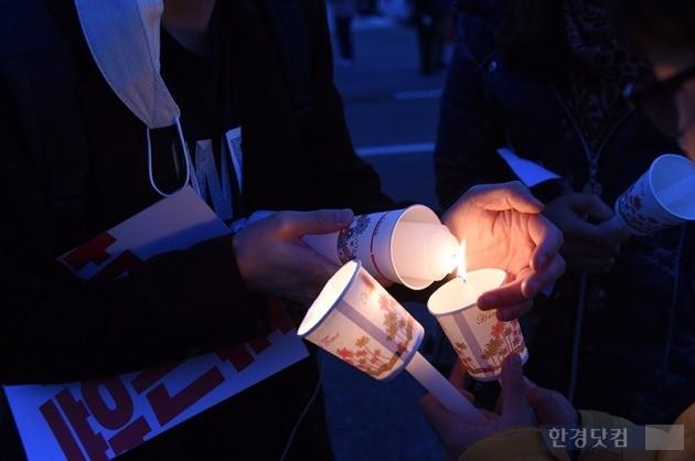 지난 12일 '최순실 국정 농단' 관련 촛불집회(민중총궐기)가 서울 도심 곳곳에서 열렸다. 광화문 광장에서 열린 집회에 참가한 시민들이 서로의 초에 불을 붙여주고 있다. / 최혁 기자 chokob@hankyung.com