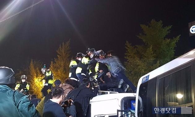 차벽 위에 오른 시민이 제지하려는 경찰과 충돌하고 있다. 사진 전형진 기자