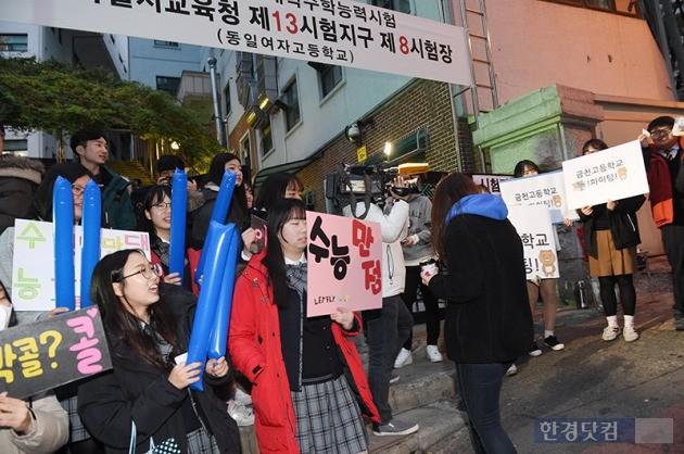 학생들이 17일 오전 수능 시험장으로 향하는 응시자들을 응원하고 있다. / 최혁 기자
