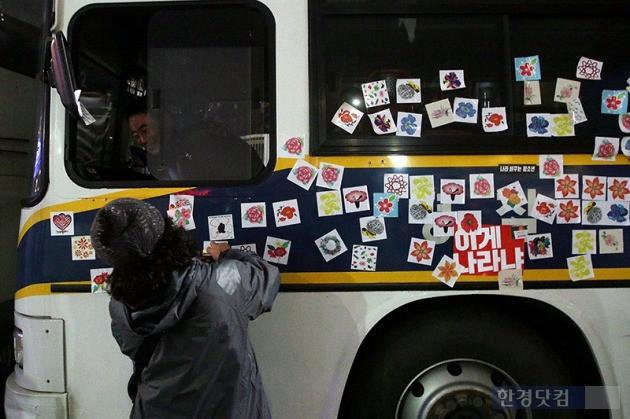 19일 오후 서울 광화문 광장에서 열린 박근혜 정부 퇴진을 요구하는 '4차 촛불집회'에서 한 시민이 경찰버스에 스티커를 붙이고 있다. / 최혁 한경닷컴 기자 chokob@hankyung.com