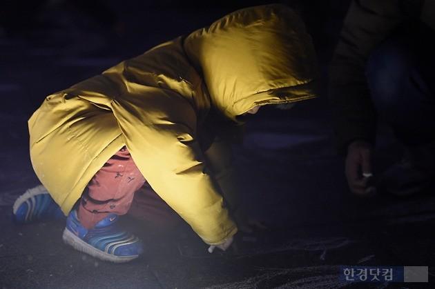 박근혜 정부 퇴진을 요구하는 '4차 촛불집회'가 19일 오후 서울 광화문 광장에서 열렸다, 어린 아이가 바닥에 촛불을 그리고 있다. / 변성현 한경닷컴 기자 byun84@hankyung.com