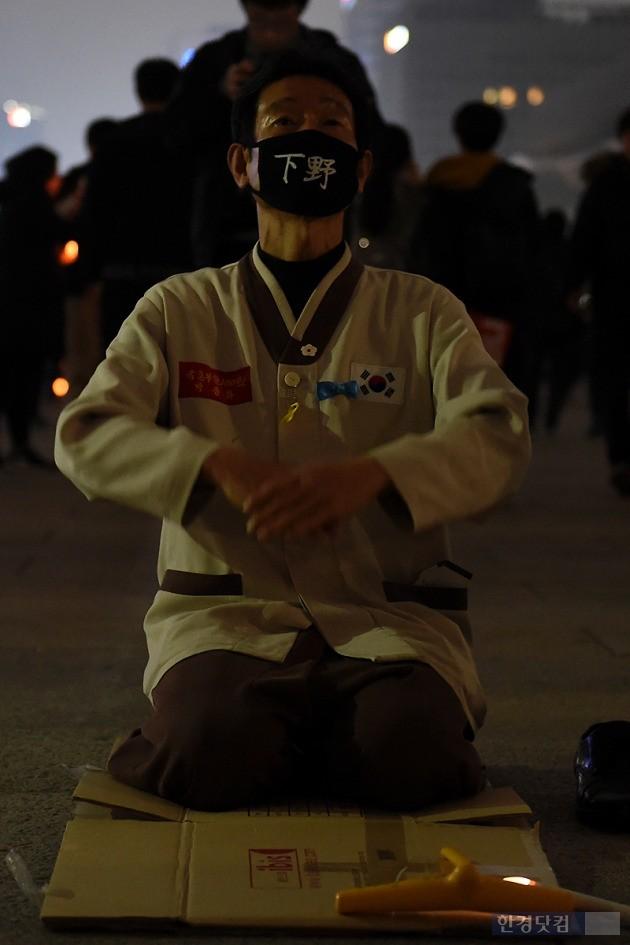 19일 오후 서울 광화문 광장에서 열린 박근혜 정부 퇴진을 요구하는 '4차 촛불집회'에 참가한 시민이 '하야'가 쓰인 마스크를 쓰고 절을 하고 있다. / 변성현 한경닷컴 기자 byun84@hankyung.com