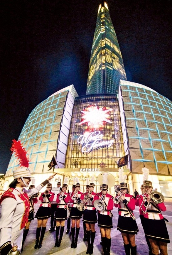 서울 잠실 롯데월드타워에 '겨울 환상세계'를 테마로 한 조명이 지난 3일 설치됐다. 롯데월드타워 에비뉴엘관 정문의 눈꽃송이 미디어파사드 앞에서 마칭밴드가 크리스마스 캐럴을 연주하고 있다. 롯데물산 제공