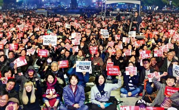 서울 광화문광장에서 지난 5일 열린 촛불집회에 참가한 시민들이 박근혜 대통령의 퇴진을 요구하는 종이카드를 든 채 시위하고 있다. 강은구 기자 egkang@hankyung.com
