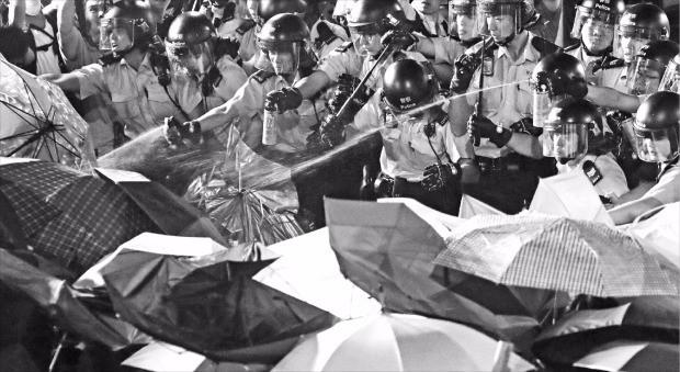중국 정부의 홍콩 탄압에 항의하는 뜻으로 검은 옷을 입은 홍콩 시위대가 지난 6일 최루 스프레이를 쏘는 경찰에게 우산으로 맞서고 있다. 홍콩AP연합뉴스