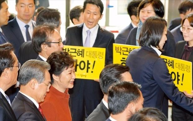 < 하야 피켓 지나치는 박 대통령 > 박근혜 대통령이 8일 '최순실 파문'과 관련한 정국 해법을 논의하기 위해 국회 본관에 들어서자 야당 의원들이 '박근혜 대통령 하야'라고 적힌 피켓을 들고 시위하고 있다. 신경훈 기자 khshin@hankyung.com