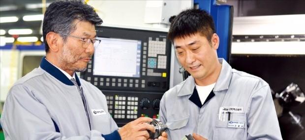 이준호 에스피지 회장(왼쪽)이 정밀 제어용 기어드 모터의 품질을 점검하고 있다. 안재광 기자
